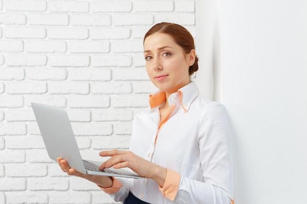 Porträt einer jungen geschäftsfrau, die laptop im büro verwendet