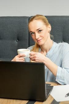 Porträt einer jungen geschäftsfrau, die laptop verwendet, der am tisch mit einer tasse kaffee in einem café sitzt