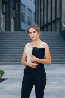 Porträt einer jungen geschäftsfrau. erfolgreiche geschäftsfrau, die draußen nahe bürogebäude steht.