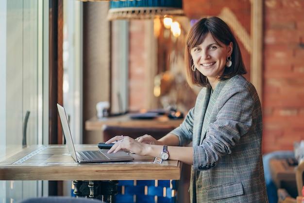 Porträt einer jungen geschäftsfrau im grauen blazer im café und im arbeiten an netbook. freiberufler, der im café arbeitet.