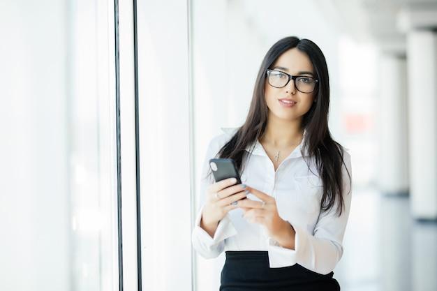 Porträt einer jungen geschäftsfrau in den gläsern, die texttelefon gegen panoramafenster tippen. geschäftskonzept