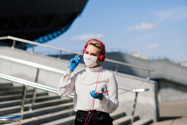 Porträt einer jungen geschäftsfrau mit telefon, notizbuch, tablette, kaffee im freien. blondes mädchen in blauen gummihandschuhen.