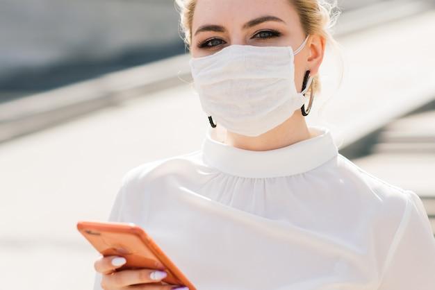 Porträt einer jungen geschäftsfrau mit telefon, notizbuch, tablette, kaffee im freien. blondes mädchen in den blauen gummihandschuhen und in der maske.