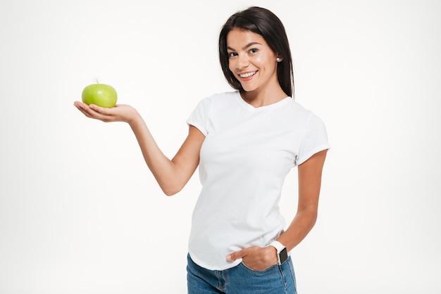 Porträt einer jungen gesunden frau, die grünen apfel hält