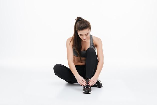 Porträt einer jungen, gesunden, sportlichen frau, die mit gekreuzten beinen auf dem boden sitzt und ihre schnürsenkel isoliert bindet