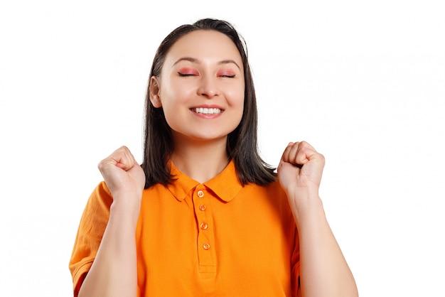 Porträt einer jungen glücklichen aufgeregten mädchenfrau in einem hellen hemd auf einem weiß