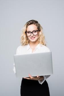 Porträt einer jungen glücklichen geschäftsfrau mit einem laptop über weißer wand
