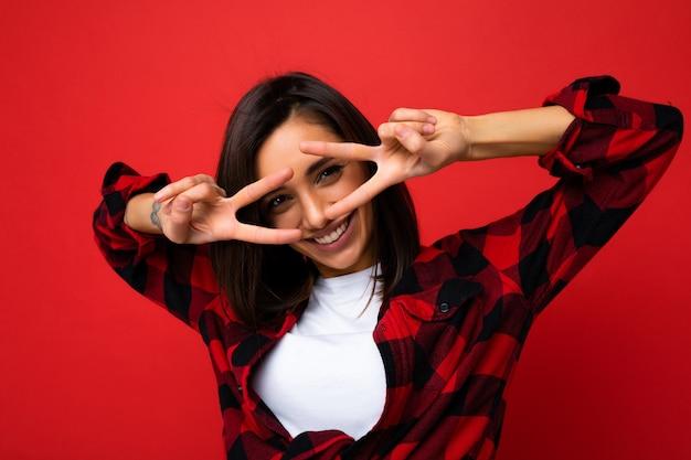 Porträt einer jungen glücklichen, positiv lächelnden, attraktiven brünetten frau mit aufrichtigen emotionen, die ein weißes t-shirt und ein rotes karohemd des hipsters einzeln auf rotem hintergrund mit leerem raum trägt