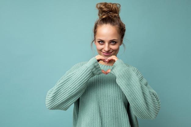 Porträt einer jungen glücklichen, positiv lächelnden, schönen blonden frau mit aufrichtigen emotionen, die einen lässigen blauen pullover trägt, der auf blauem hintergrund mit kopienraum isoliert ist und mit händen in herzform gestikuliert
