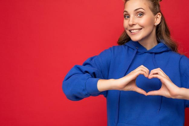 Porträt einer jungen glücklichen, positiven, schönen blonden frau mit aufrichtigen emotionen, die einen trendigen hellblauen hoodie trägt, der auf rotem hintergrund mit kopienraum isoliert ist und herzform mit den händen zeigt