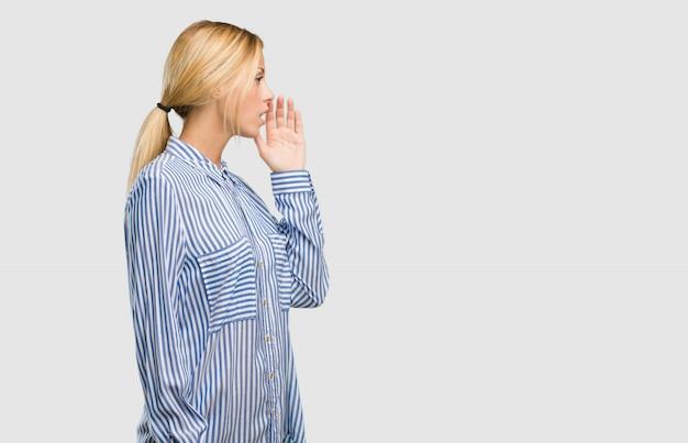 Porträt einer jungen hübschen blonden frau, die den klatschuntergrund flüstert und versucht, nicht gehört zu werden