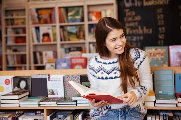 Porträt einer jungen hübschen frau, die in der bibliothek ein buch steht und liest