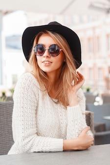 Porträt einer jungen hübschen frau in einem schwarzen hut und einer runden sonnenbrille schöne frau sitzt im sommercafé