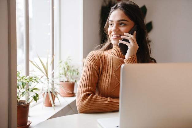 Porträt einer jungen hübschen schönen frau, die im café drinnen unter verwendung des laptop-computers sitzt, der durch handy spricht.