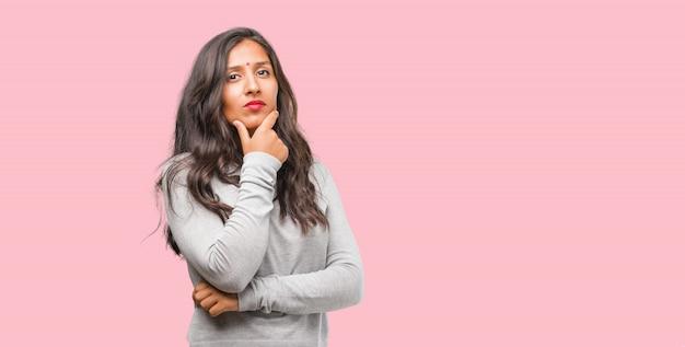 Porträt einer jungen indischen frau, die oben denkt und schaut, verwirrt über eine idee