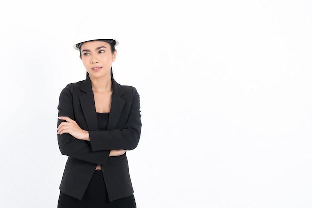 Porträt einer jungen ingenieurin mit weißem schutzhelm im anzug, die lächelnd in die kamera schaut, im studio isoliert auf weißer oberfläche aufgenommen