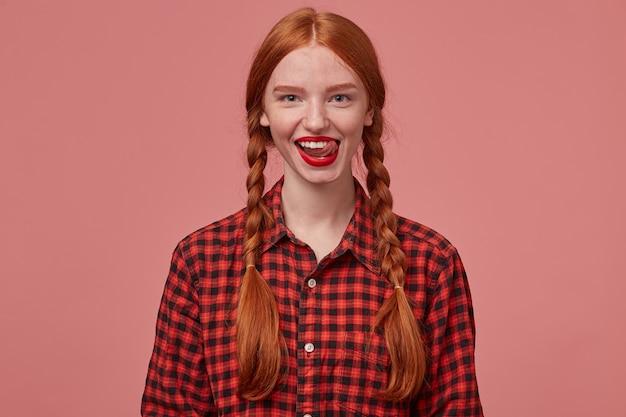 Porträt einer jungen ingwerfrau mit zöpfen, lächelt breit, während sie mit ihrem freund flirtet