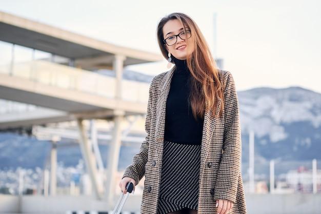 Porträt einer jungen intelligenten geschäftsfrau am internationalen flughafen mit koffer