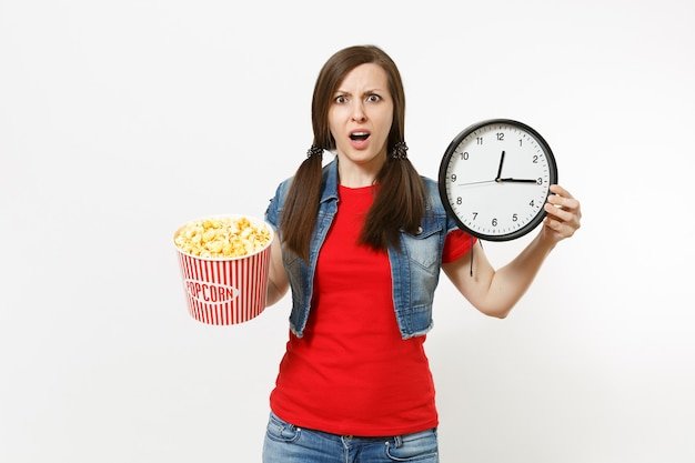 Porträt einer jungen irritierten unzufriedenen brünetten frau in freizeitkleidung, die einen filmfilm sieht, einen eimer popcorn und einen runden wecker isoliert auf weißem hintergrund hält. emotionen im kinokonzept.