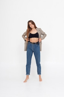 Porträt einer jungen kaukasischen attraktiven frau mit langen braunen haaren in blue jeans, schwarzer spitze und anzugjacke auf weißem hintergrund. dünne hübsche dame posiert im studio mit nackten füßen