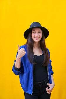 Porträt einer jungen kaukasischen frau im schwarzen hut und in der blauen jacke, daumen hoch