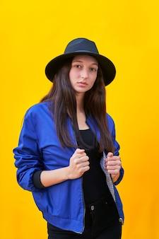 Porträt einer jungen kaukasischen frau im schwarzen hut und in der blauen jacke, die ihre jacke mit ihren händen hält