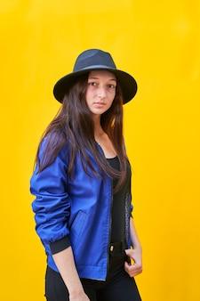 Porträt einer jungen kaukasischen frau im schwarzen hut und in der blauen jacke.