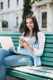 Porträt einer jungen kaukasischen frau mit langen dunklen haaren, die ihr lächelndes smartphone betrachten, während sie draußen auf einem strand mit einem laptop auf ihren beinen sitzen.