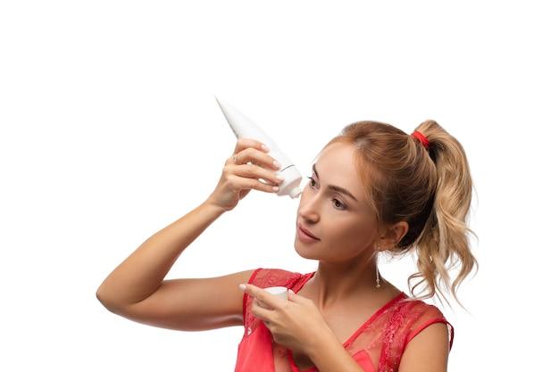 Porträt einer jungen kaukasischen frau mit mittelblondem haar ist in einen pferdeschwanz geflochten, mit schöner klarer haut wird ein anti-falten-verfahren mit spezieller creme durchgeführt