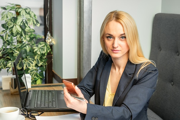 Porträt einer jungen kaukasischen geschäftsfrau mit einem smartphone und einem laptop am tisch