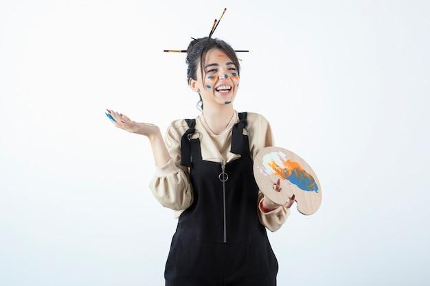 Porträt einer jungen künstlerin, die mit einem gemalten gesicht aufwirft und holzpalette hält.