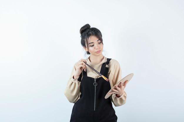 Porträt einer jungen künstlerin, die pinsel mit einer holzpalette hält.