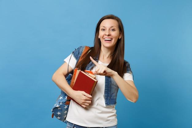 Porträt einer jungen lachenden studentin mit rucksack, die den zeigefinger beiseite auf kopienraum zeigt und schulbücher auf blauem hintergrund isoliert hält. bildung im hochschulkonzept der high school.