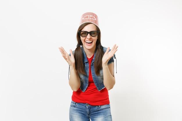 Porträt einer jungen lächelnden attraktiven frau in 3d-brille und freizeitkleidung mit eimer für popcorn auf dem kopf, die filmfilm anschaut und die hände lokalisiert auf weißem hintergrund ausbreitet. emotionen im kino.