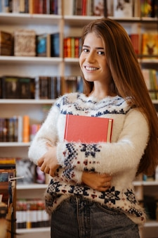 Porträt einer jungen lächelnden frau, die ein buch hält, während sie in der bibliothek steht
