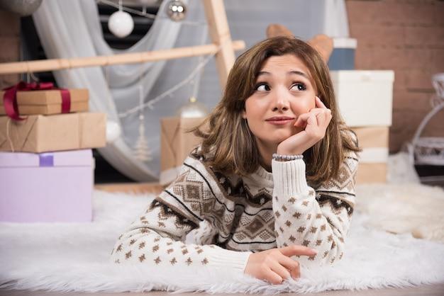 Porträt einer jungen lächelnden frau, die im weihnachtsinnenraum auf dem boden liegt