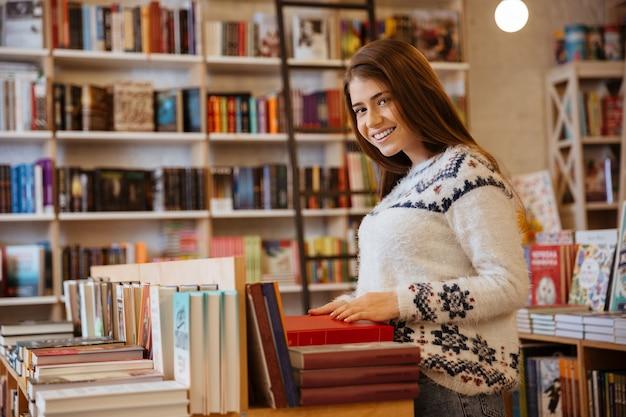 Porträt einer jungen lächelnden frau, die in der buchhandlung nach einem buch sucht