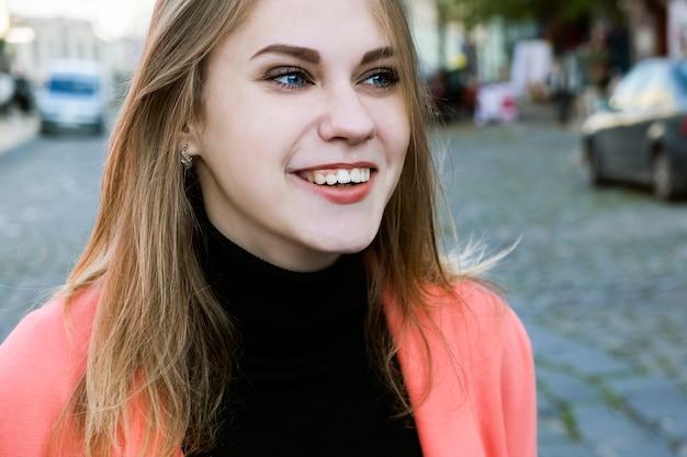Porträt einer jungen lächelnden frau in einer hellen rosa jacke, die die straße an einem warmen herbsttag entlang geht