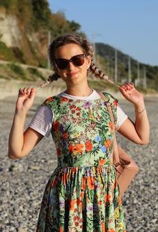 Porträt einer jungen lächelnden frau mit sonnenbrille, die ihre zöpfe hält und in die kamera schaut