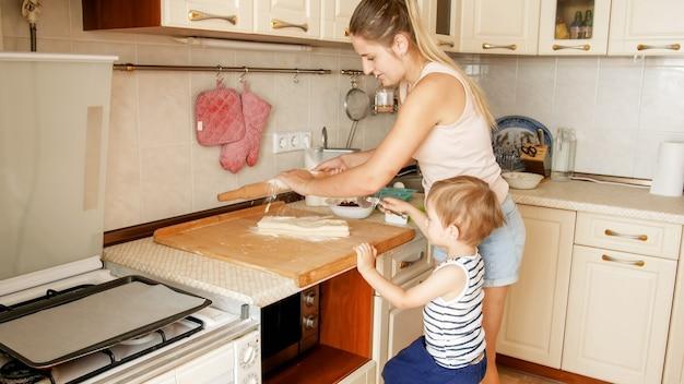 Porträt einer jungen lächelnden mutter, die ihrem 3 jahre alten kleinkind das backen und backen von keksen in der küche beibringt