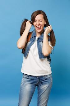 Porträt einer jungen lustigen verrückten studentin in denim-kleidung mit rucksack, die zungentäter zeigt, die pferdeschwänze einzeln auf blauem hintergrund halten. ausbildung an der hochschule. kopieren sie platz für werbung.