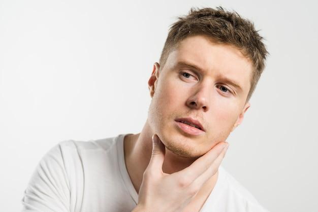 Porträt einer jungen mannholdinghand unter seinem kinn, das weg schaut