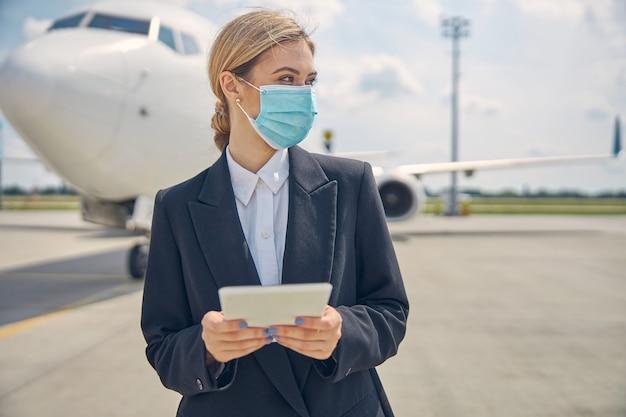Porträt einer jungen mitarbeiterin einer fluggesellschaft mit einem tablet-computer, der in die ferne starrt