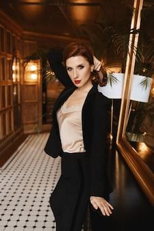 Porträt einer jungen modelfrau mit perfektem make-up und vollen roten lippen, die eine satinbluse und einen trendigen anzug trägt, der im luxuriösen interieur posiert