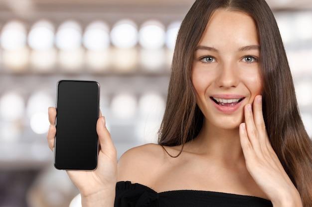 Porträt einer jungen modernen frau, die einen smartphone hält