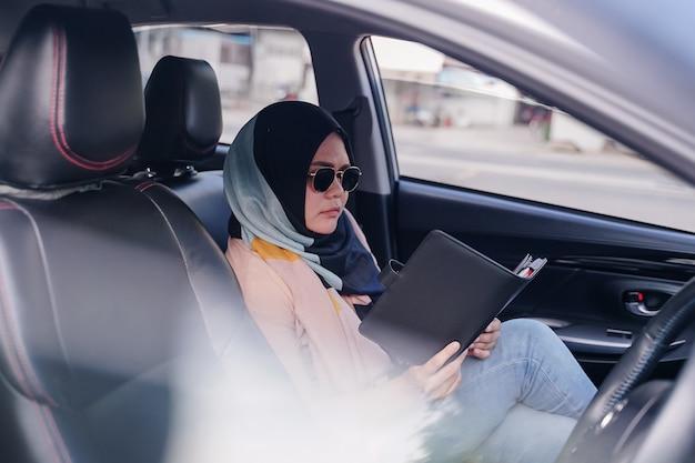 Porträt einer jungen moslemischen geschäftsfraulesung auf dem rücksitz des autos.