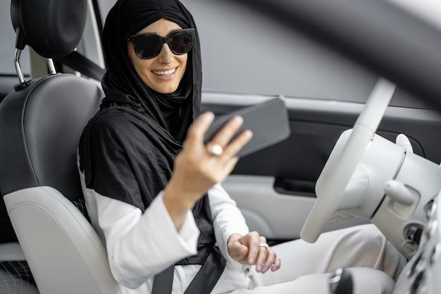 Porträt einer jungen muslimischen geschäftsfrau mit einem hijab telefoniert beim autofahren. konzept der globalisierung und modernisierung der islamischen gesellschaft und frauenrechte