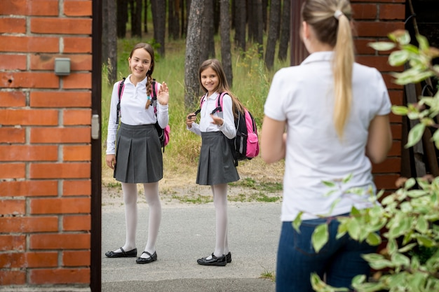 Porträt einer jungen mutter, die ihre kinder zur schule sieht und ihnen zuwinkt