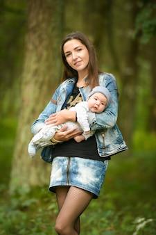 Porträt einer jungen mutter mit einem baby auf der straße. baby auf den händen einer jungen lächelnden mutter in einer frühlingsgasse.
