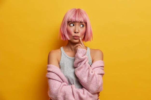 Porträt einer jungen nachdenklich überraschten asiatischen frau mit rosigem haar, hält finger auf gesicht und sieht verwundert zur seite, trägt warmen strickpullover